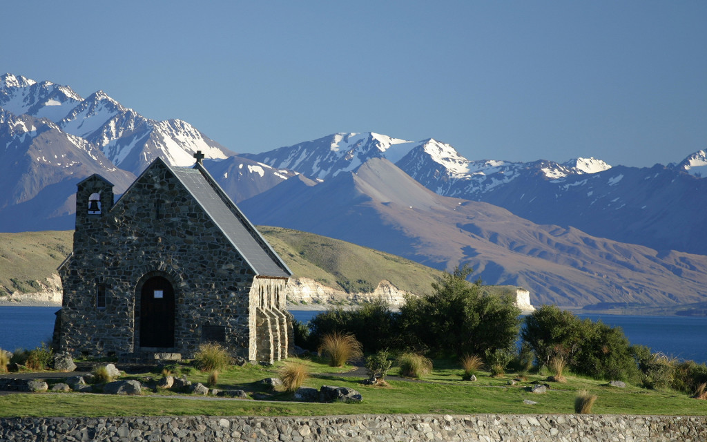 The Church of the Good Shepherd on the shore of Lake Tekapo in New Zealand against a landscape of snowy mountains.