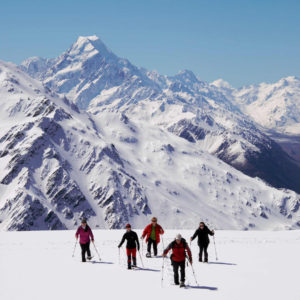 A group snowshoeing on a mountain snow field near Aoraki Mount Cook National Park.