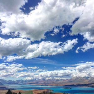 Views over turquoise blue Lake Tekapo with stunning cloud formations above.