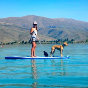 A paddle board enthusiast with her dog on Lake Ruataniwha near Twizel.