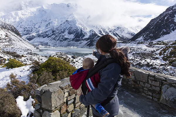A woman holds a baby and takes in the winter view from the Hooker Valley Track.